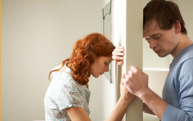 Frustrated-couple-on-either-side-of-a-wall