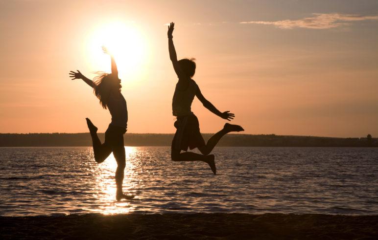 Millennial-couple-jumping-for-joy-at-beach